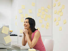 woman sitting in kitchen planning/dreaming with sticky notes all around