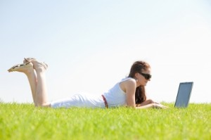 Young Female Lying On The Grass In The Park Using A Laptop